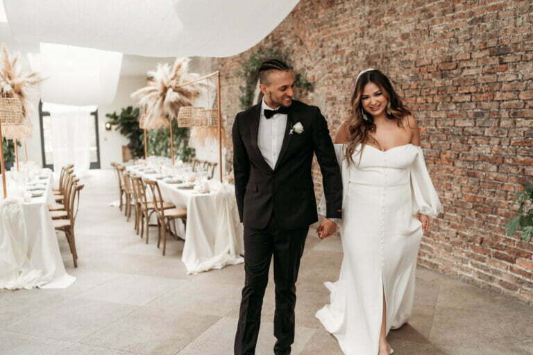 Couple holding hands, smiling as they walk into the reception room